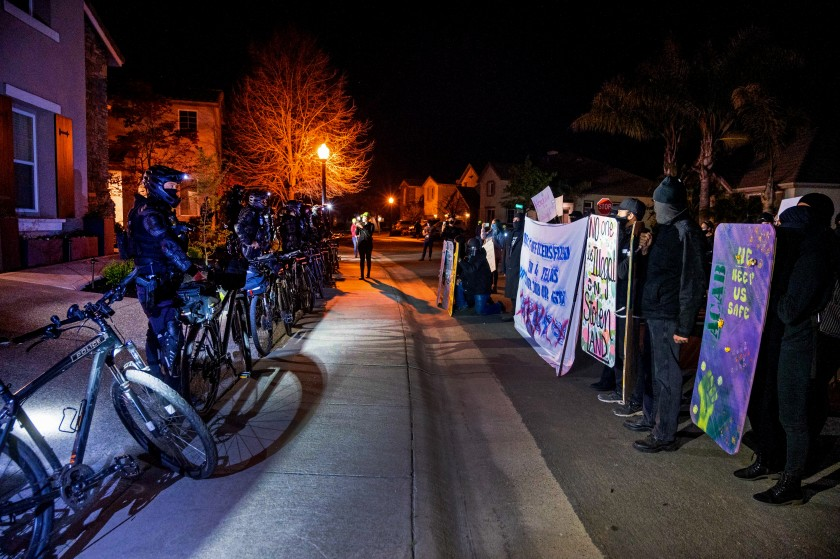 A row of protesters faces off with a row of police officers on a suburban street at night.
