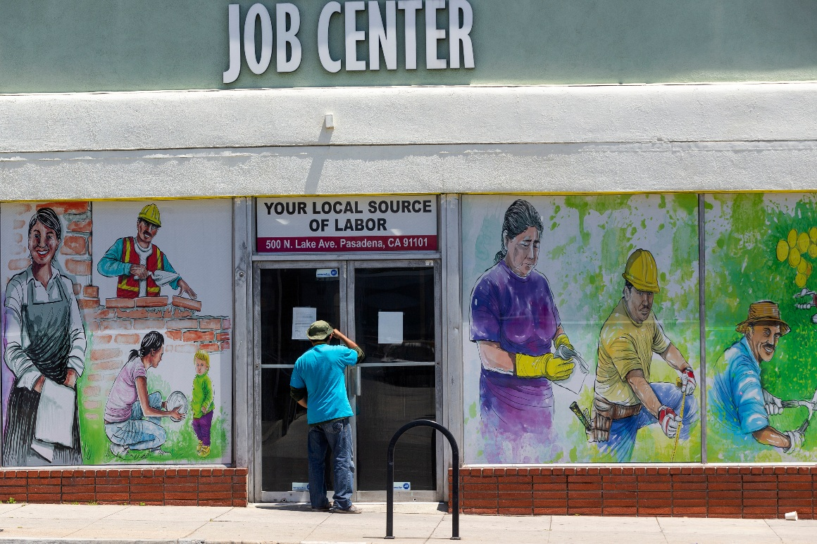 A person looks inside the closed doors of a job center during the coronavirus pandemic.
