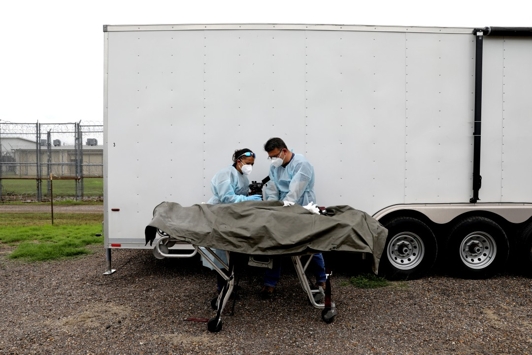 Two forensics workers stand over a body on a gurney beside a trailer