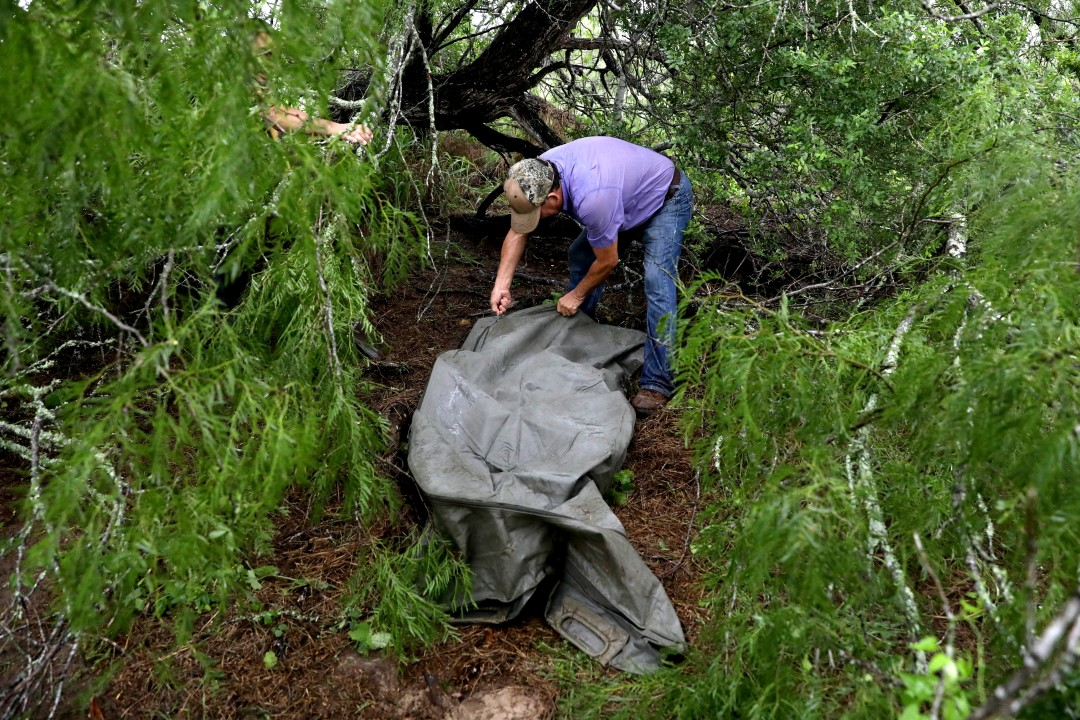 A man tends to a body found near a tree