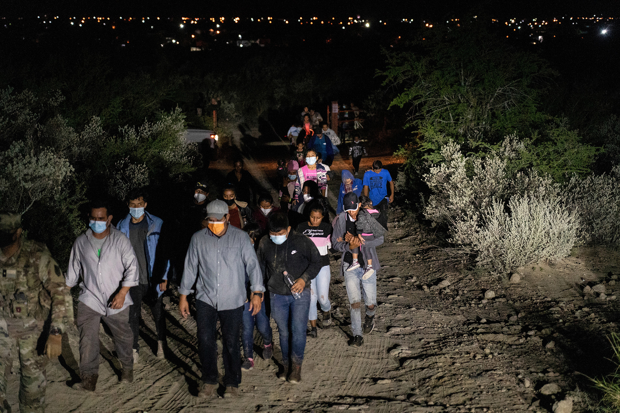 Migrant families are escorted by the US National Guard after crossing the Rio Grande river into the United States from Mexico on Aug. 14, 2021.