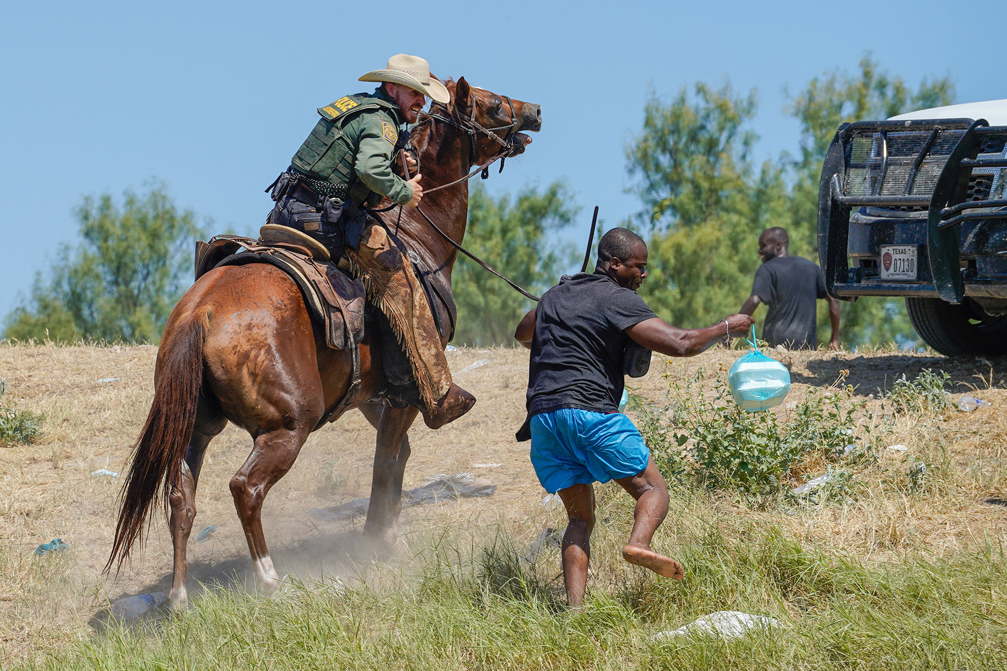 A Border Patrol agent on horseback attempting to stop a migrant from entering the encampment near Del Rio on September 19, 2021.