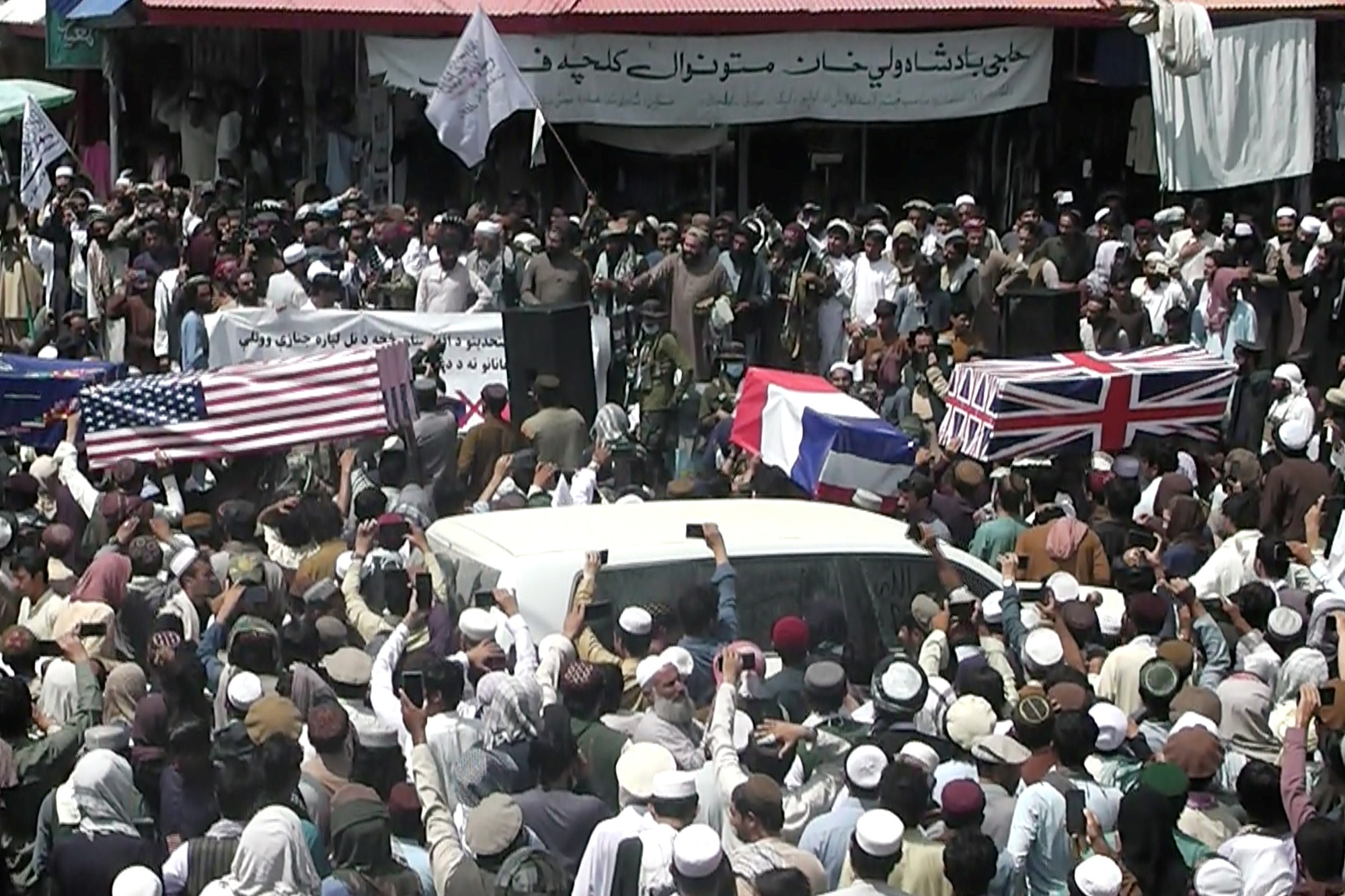 Taliban supporters carry makeshift coffins with the US, Great Britain and French flags draped on them in Khost, Afghanistan on August 31, 2021.