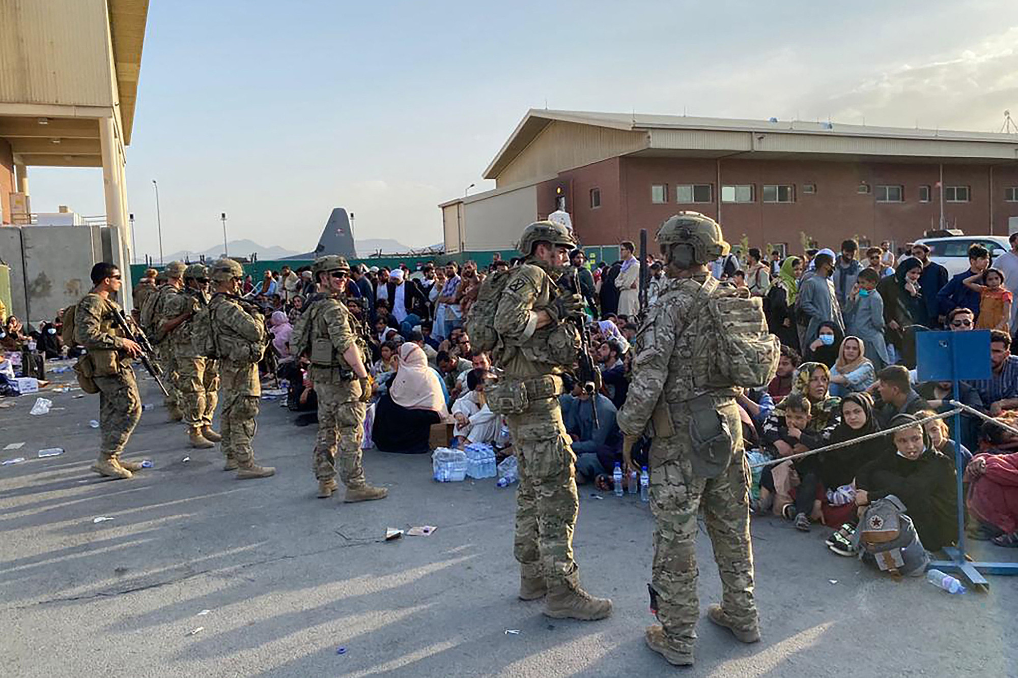 US soldiers stand guard as Afghan people wait to board a US military aircraft to leave Afghanistan, at the military airport in Kabul after Taliban's military takeover of Afghanistan.