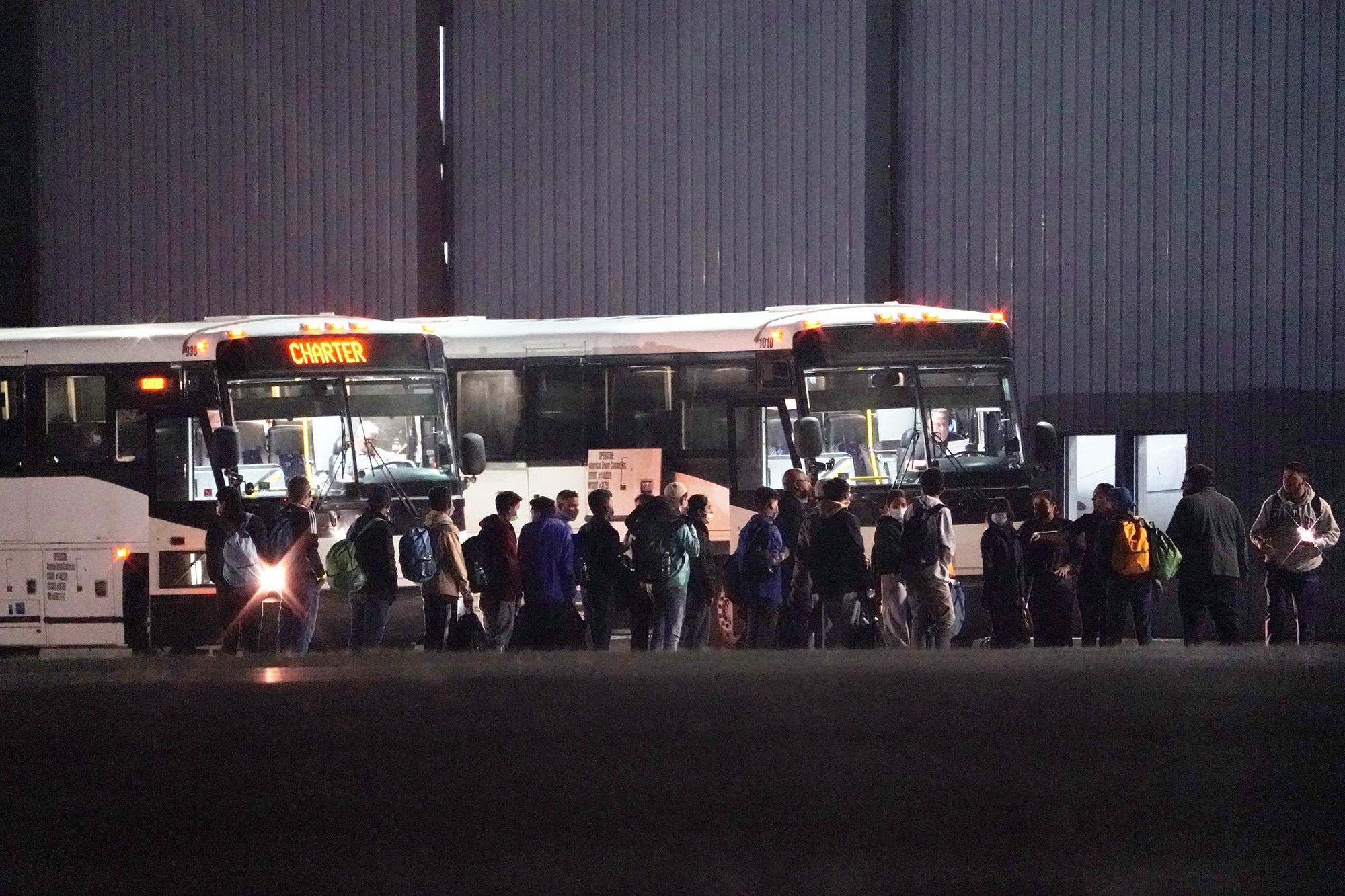Migrants board a bus.